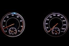 Het dashboard van de auto is het gloeien blauw met rode pijlen bij nacht met een snelheidsmeter, tachometer en andere hulpmiddele stock foto