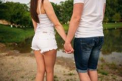 Het dateren in park Liefdepaar die zich op grond dichtbij het meer verenigen Romaans en liefde Royalty-vrije Stock Fotografie