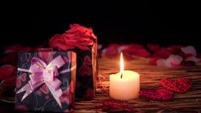 Het dateren van Valentine-dagdecoratie met giftdozen, kaars het branden en bloemblaadjes stock videobeelden