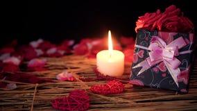 Het dateren van Valentine-dagdecoratie met giftdozen, kaars het branden en bloemblaadjes stock video