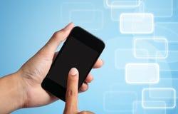 Het de aanrakingsscherm van de hand aan slimme telefoon Stock Foto's