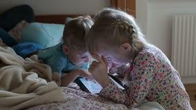 Het de blondejongen en meisje in pyjama's gebruiken tablet en het spreken stock videobeelden