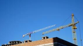 Het de bouw stationaire hijstoestel draait in aanbouw dichtbij het gebouw Tegen de blauwe hemel stock video