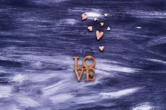 Het de dagconcept van Valentine ` s, de houten harten en het woord houden van op een blauwe houten achtergrond, natuurlijk licht, Stock Fotografie