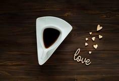 Het de dagconcept van Valentine ` s, de witte kop met koffie en de houten inschrijving houden van en harten op houten oppervlakte Royalty-vrije Stock Foto's