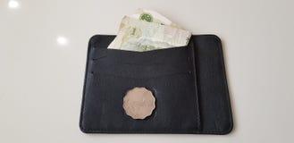 Het de dollarsmuntstuk van Hongkong legt op zwarte leerportefeuille met één yuansbankbiljet stock afbeelding