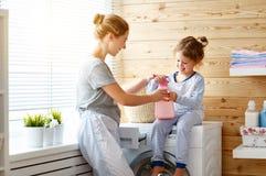 Het de gelukkige huisvrouw en kind van de familiemoeder in wasserij met washin stock foto's