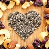 Het de gemengde vruchten, de noten, en hart van het chiazaad op houten korrel scherpe raad, schikten in vierkant voor sociale med Stock Fotografie