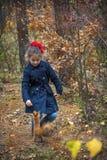 In het de herfstbos, voedt een klein meisje een eekhoorn met noten royalty-vrije stock afbeelding