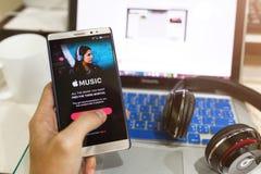 Het de holdingsscherm van de mensenhand van Apple-muziek app wordt geschoten die op Andro tonen die stock afbeelding