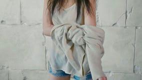 Het de jeugdmodel kleedt omhoog de sweater over witte steenmuur Stock Afbeelding
