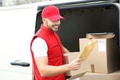 Het de jonge envelop en pakket van de koeriersholding dichtbij bestelwagen stock afbeeldingen