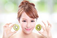 Het de kiwifruit van de vrouwenholding behandelt haar ogen Royalty-vrije Stock Afbeeldingen