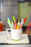 Het de kleurrijke pennen en notitieboekje van bureauelementen Stock Foto's