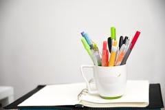 Het de kleurrijke pennen en notitieboekje van bureauelementen stock afbeelding