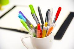 Het de kleurrijke pennen en notitieboekje van bureauelementen Royalty-vrije Stock Foto's