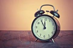 Het de klok van ` s twaalf o ` reeds, tijd om voor lunch, uitstekende oude zwarte metaalwekker te ontwaken Royalty-vrije Stock Afbeelding