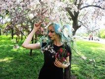 Het de lentemeisje met groen haar bevindt zich onder bloeiende kersenboom, die bloeit royalty-vrije stock afbeeldingen