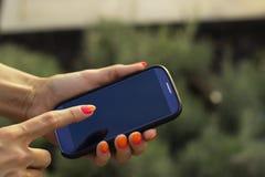 Het de mobiele telefoon en punt van de vrouwengreep van haar vinger Stock Afbeelding