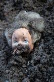 Het de poppenhoofd van het brandwondmeisje ligt in een stapel van as Stock Fotografie