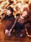 Het de schijfjockey en blonde genieten van muziek bij nachtclub stock fotografie