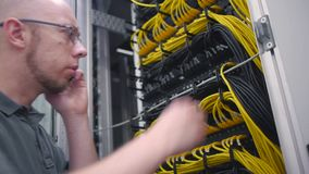 Het de serverrek die van kerelcontroles op de telefoon spreken stock videobeelden