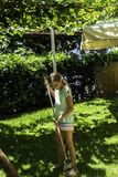 Het de tienerjongen en meisje die droge de herfstbladeren harken en werpen in oude metaalkruiwagen op groene grasachtergrond in d royalty-vrije stock fotografie