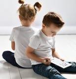 Het de twee jonge geitjesjongen en meisje in witte t-shirts en jeans zitten dicht bij elkaar en spelen slagschip stock foto