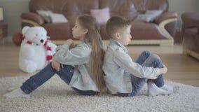 Het de tweelingenjongen en meisje zitten op de vloer van woonkamer rijtjes boos aan elkaar Broer en zusterverhouding stock video