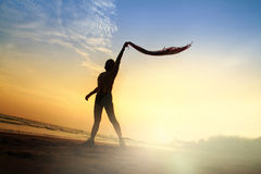 Het de vrouwenspel van de silhouetlevensstijl stelt op strandzonsondergang Royalty-vrije Stock Afbeelding