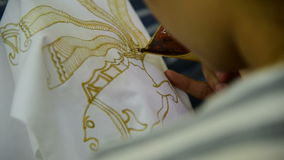 Het in de was zetten van de patronen op de textiel voor batik