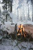 In het de winterbos op een picknick bij de brandende brand Stock Afbeelding
