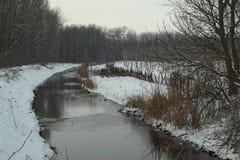 Het de winterlandschap met bevroren kanaal en sneeuwt rond allen Stock Afbeelding