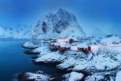 Het de winterlandschap met huizen in dorp, stadsverlichting, sneeuwbergen, overzees, blauwe bewolkte hemel dacht in water na bij  royalty-vrije stock fotografie