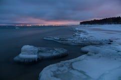 Het de winterlandschap van ijzige zeekust en stad steekt 's nachts aan stock fotografie
