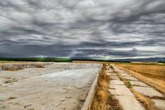 Het de zomerlandschap met onweerswolken en het tarwegebied na de stralen van de oogstzon over het gebied en de bosopslag plaatsen Royalty-vrije Stock Afbeelding