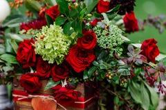 Het decor van de huwelijkslijst: bloeit samenstelling met rozen, bessen, kruiden en groen die zich in houten doos bevinden Bruids Royalty-vrije Stock Foto