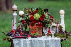 Het decor van de huwelijkslijst: stoelen en kaarsen, bloemen, ceramische schotels met vruchten, die zich op het het kanttafelklee Stock Afbeeldingen