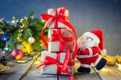 Het decoratieve Santa Claus-dragen stelt op de feestelijke donkere achtergrond met Kerstboom, lichten en decor op oud houten BO v Stock Fotografie