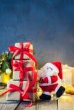Het decoratieve Santa Claus-dragen stelt op de feestelijke donkere achtergrond met Kerstboom, lichten en decor op oud houten BO v Stock Afbeelding
