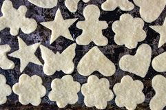 Het deeg in de suiker op een donkere achtergrond bloeit de sterren van hartenmensen stock afbeeldingen