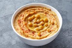 Het deeg dichte omhooggaand van het Middenoosten van de Hummus eigengemaakte onderdompeling met paprika, tahini, en olijfolie royalty-vrije stock afbeelding
