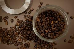 Het deksel en de koffiebonen van de koffiebus op de lijst worden verspreid die stock fotografie