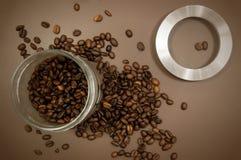 Het deksel en de koffiebonen van de koffiebus op de lijst worden verspreid die royalty-vrije stock fotografie