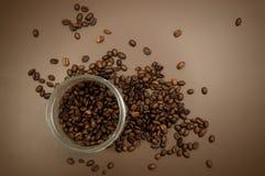 Het deksel en de koffiebonen van de koffiebus op de lijst worden verspreid die stock foto