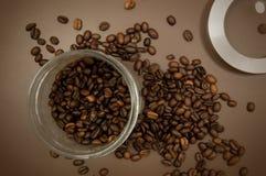 Het deksel en de koffiebonen van de koffiebus op de lijst worden verspreid die royalty-vrije stock foto's