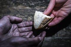 Het delen van hoop De hand geeft brood aan bedelaar stock afbeeldingen