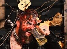 Het demon met hoornen en kwaad glimlachgezicht drinkt aal Halloween-partijconcept De mens die enge make-up dragen houdt bier royalty-vrije stock afbeeldingen