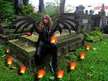 Het demonmeisje zit op het graf in de begraafplaats Stock Foto