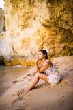 Het denken alleen voelt de Latijnse meisjeszitting op zand bij strand en het bekijken oceaan De zomerroeping Royalty-vrije Stock Afbeeldingen